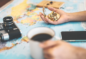Side view female hands planning vacation with world map and vintage nautical compass - Travel adventure lifestyle people and discovering destinations concept