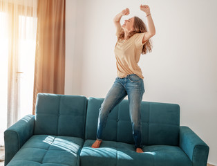 Foto op Canvas Dance School Happy young woman in a T-shirt and jeans dancing on a blue sofa in the living room at home, buying real estate and furniture concept