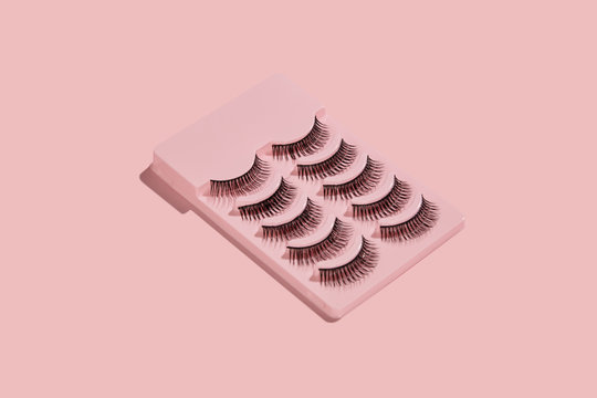 a pink box with five pairs of false lashes on pink background