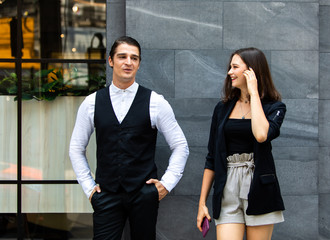 Business colleagues couple walking on street while talking to each other. Young happy business couple walking outdoor office building