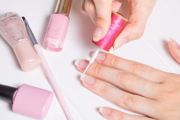 A woman paints her nails. The girl applies nail Polish. Manicure, French, nail care. Nail salon, procedure, SPA. Home nail care. Manicure tools. Beauty, lifestyle, Glamour