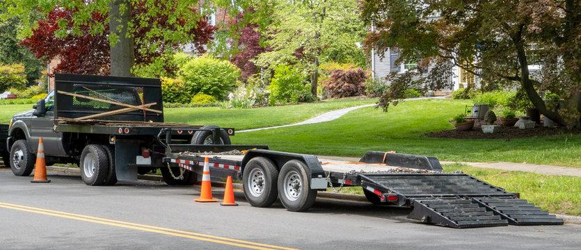 Landscaping truck with empty flatbed trailer with ramp parked on residential neighborhood street.