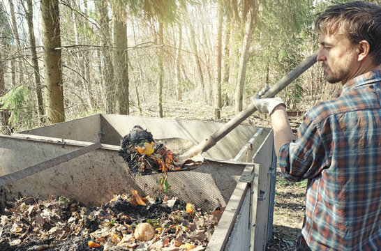 Local farmer holding shovel full of compostable food scraps over compost heap. Composting, permaculture, zero waste gardening, sustainable living. Kitchen and garden waste leftovers to fertilizer.