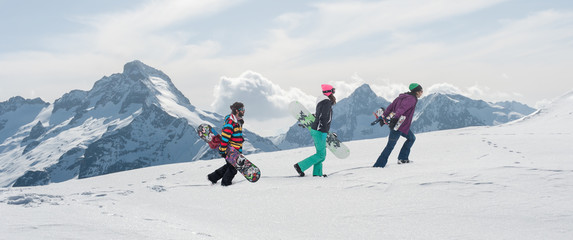 The group freeride snowboarders hike and carry their snowboards boards