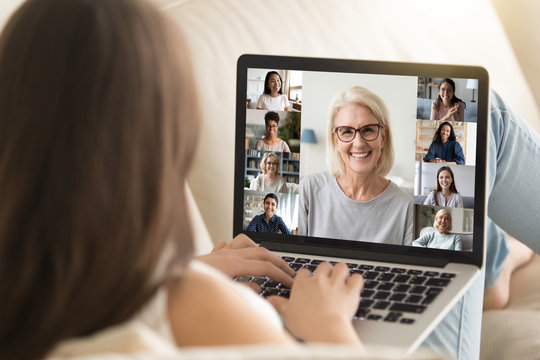 Laptop screen view mature 50s lady lead group videocall distant talk with different ethnicity age women. View over girl shoulder sit on sofa involved at remote chat, empowerment movement club concept