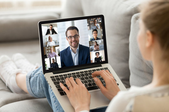 Concept of group videocall using webcam and laptop modern technologies and distant communication. View over girl shoulder resting on couch holding on lap notebook advertise worldwide virtual chat app
