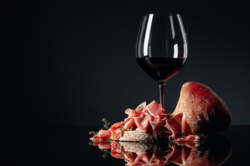 Fototapete - Prosciutto with ciabatta, red wine and thyme on a black background.
