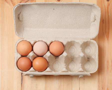 several chicken eggs in a cardboard box on a wooden textured background. the view from the top