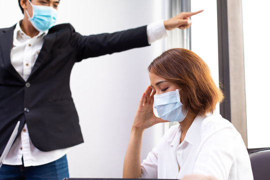 You are fired concept. Manager finger showing the exit door. Depressed woman employee being fired at office. Employee was fired due to problem from coronavirus covid 19 outbreak