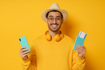 Young man student tourist holding passport and smart phone with travel app for buying tickets online, isolated on yellow background