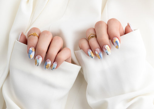 Woman's hand with fashionable nails holding fabric.
