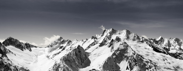 Fototapete - Panorama of snow-capped mountain peaks and sky with clouds