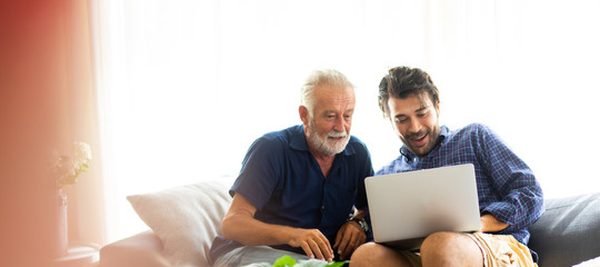 Father and son family time together at home concept. Smiling old father and happy son sitting on...