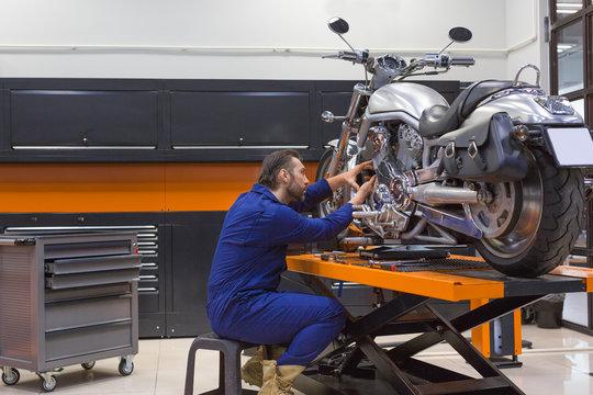 Man repairing motorcycle in a workshop.