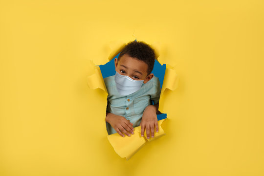 Sad African American boy celebrates his birthday by blowing up firecracker in medical mask protecting against coronavirus virus on yellow torn paper wall background. Concept of bad birthday.