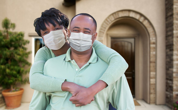 Loving African American Couple Hugging Wearing Medical Face Masks In Front of House