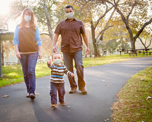 Happy Mixed Race Ethnic Family Walking In The Park Wearing Medical Face Mask