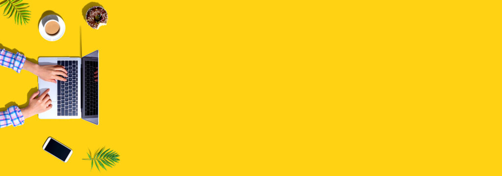Woman using a laptop computer with a donut and a cup of coffee