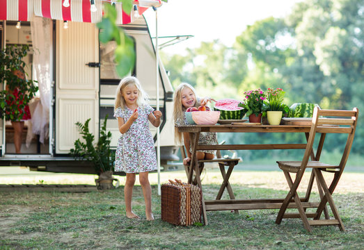 Two blond sisters in light dresses having the picnic at camping with marshmallows