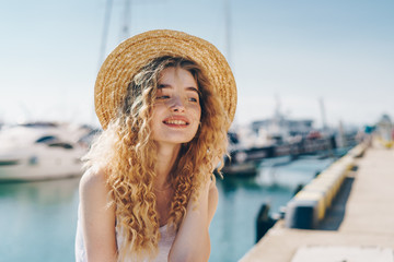 curly blonde in a straw hat sits on the background of the seaport and gently smiles