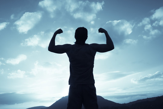 Confident man flexing is arms facing the sunset sky.