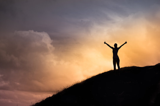 Happy female standing on a hill facing the sunset putting her arms, thumbs up feeling happy, energized, and free. Finding you inner strength concept.