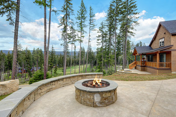 Stone patio with fire pit and large stone wall with sitting space.