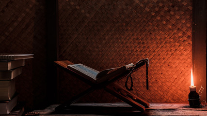 Quran and Islamic prayer beads in a rustic house room lit by traditional oil lamp. Concept of Ramadan in rural area.
