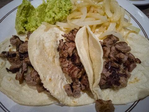 tacos de carne asada, papas fritas y guacamoles.