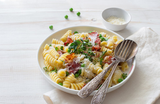 Italian pasta with fried bacon and green peas closeup