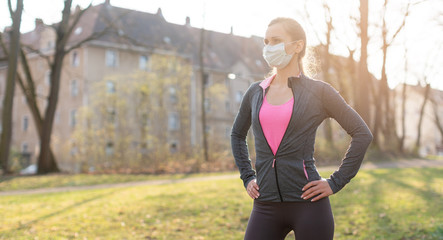 Fit woman during health crisis exercising outdoors wearing mask Fotomurales
