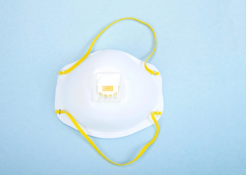 Top view flat lay of one N95 medical grade mask laying on light blue background.