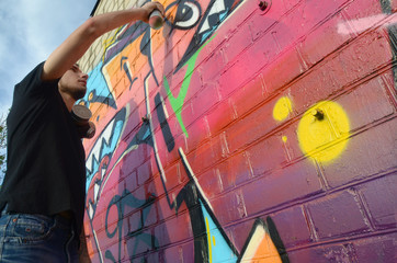 Young graffiti artist with backpack and gas mask on his neck paints colorful graffiti in pink tones...