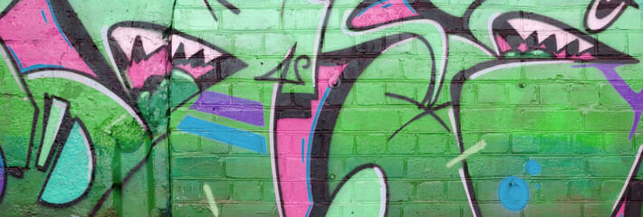 Abstract colorful fragment of graffiti paintings on old brick wall in green colors. Street art...