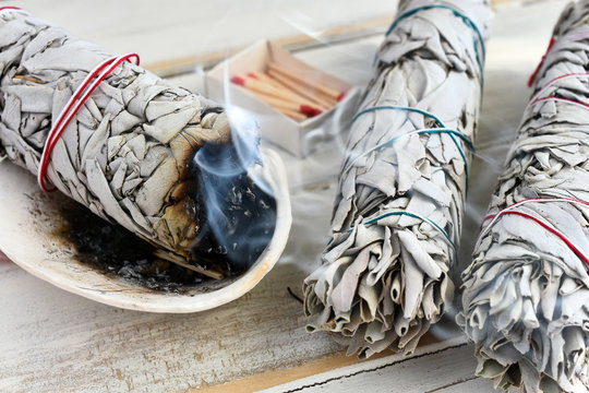 A close up image of a burning white sage smudge stick used for energy clearing and healing.