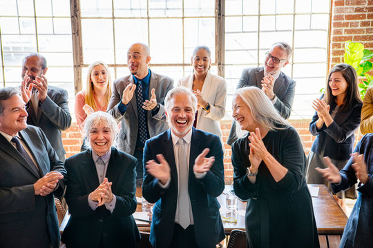 Team of business people clapping