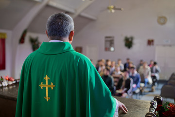 Catholic priest standing on a church podium and preaching, religion