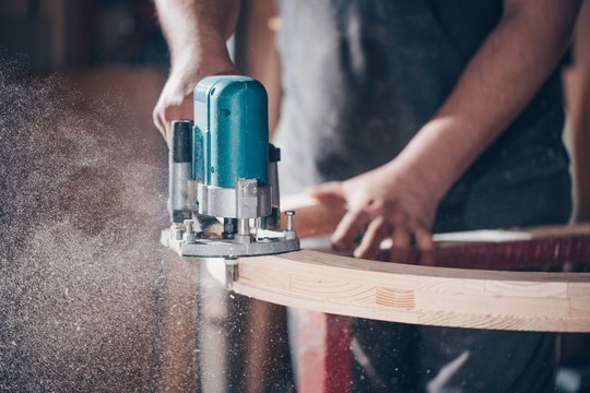 Joinery, woodworking and furniture making, professional carpenter cutting wood in carpentry shop, industrial concept