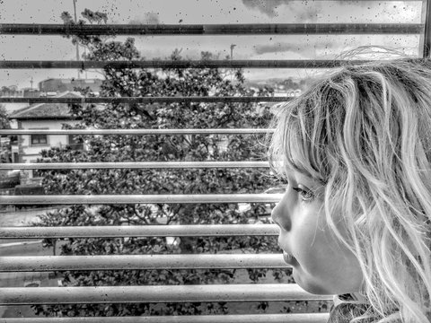 Close-up Of Girl Looking Through Blinds At Home
