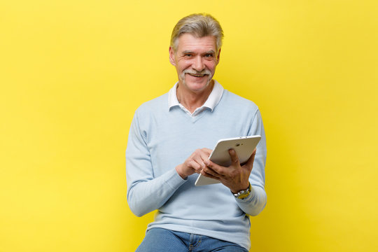 Smiling senior man reading news on digital tablet. Cheerful excited mature male using portable computer, yellow studio background