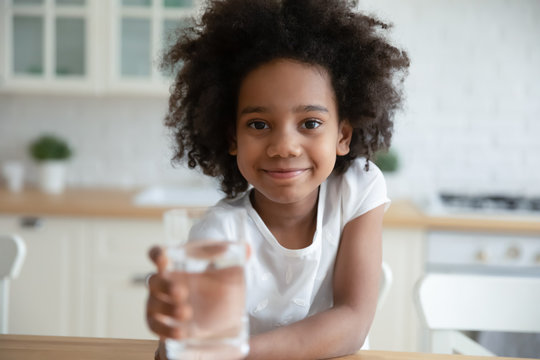 Portrait of smiling little African American girl recommend drink still mineral water, happy small biracial child offer crystal clear aqua for daily body refreshment, healthy lifestyle concept