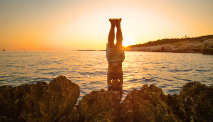 SUN FLARE: Golden evening sunbeams shine on man diving head first into the ocean Wall mural