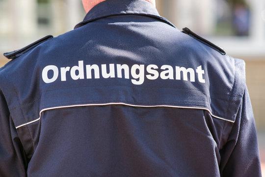 Konzept Ordnung und Sicherheit: Nahaufnahme des Rückens eines Mitarbeiter des Ordnungsamtes in Uniform auf Streife - selektiver Fokus