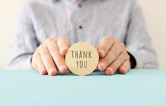 male hands holding sign with the text thank you
