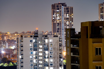 Aerial shot of buildings at night in Gurgaon with smaller buildings in front and skyscrapers in the background Fototapete