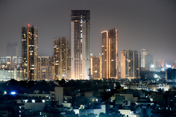 High rise multi story skyscrapers lit up at night with small houses in the foreground at night in gurgaon delhi Fototapete
