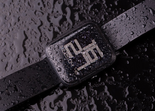 Berlin, Germany - April 29, 2019: Smart watch Xiaomi Huami Amazfit Bip close-up. Waterproof smart watch with water drops on a dark background.