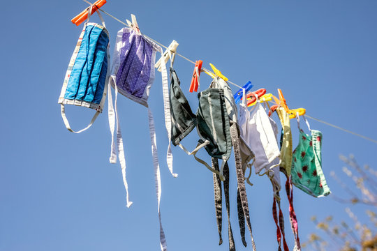 Washed makeshift fabric face masks are drying on a clothes line