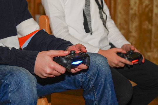 boys are playing Sony PlayStation. Boy playing with a joystick. A boy enjoy playing game on Sony PlayStation at home.