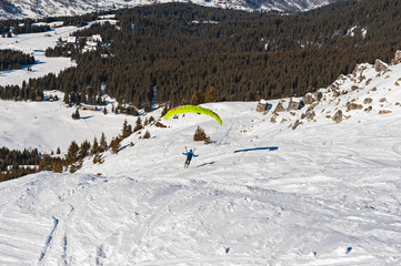 Wall Mural - Paraglider taking off from a snowy alpine slope